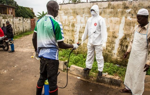 A health worker being disinfected after treating a patient in Freetown, Sierra Leone. / Michael Duff.,Ebola