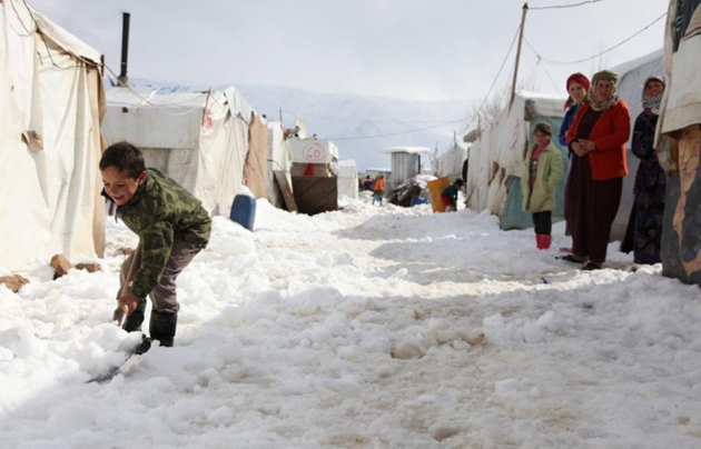 Boy helps clearing snow at a Syrian refugee camp. / World Vision,Syria camp boy