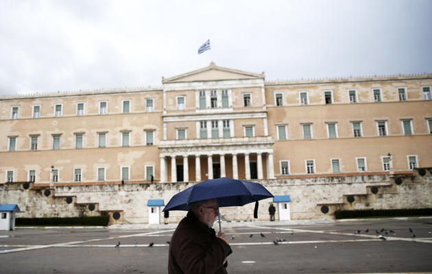 A man holding an umbrella makes his way in front of the Greek parliament during rainfall in Athens. / Reuters,greece parliament man rain