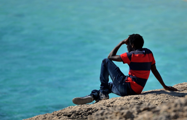A man looks to the sea in Lampedusa. / Getty,refugee lampesuda sicily