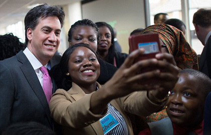 Labour leader Ed Miliband poses for a 'selfie' during a visit to a church in London. / PA