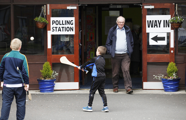 Children play with hurling sticks outside a polling station in West Belfast, Northern Ireland, the day of the election. / AP,children, polling station