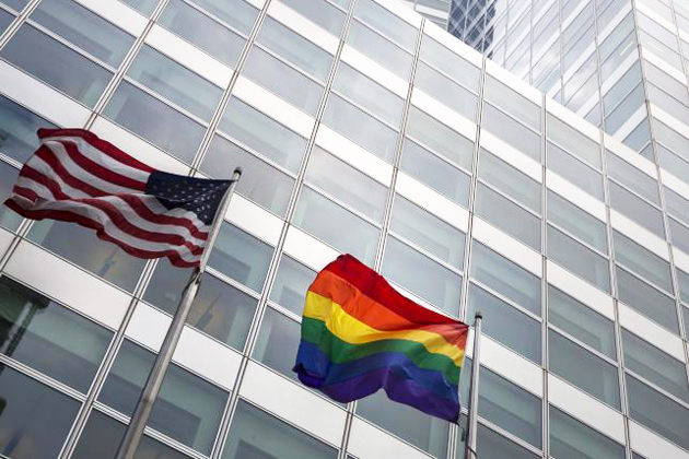 A gay pride rainbow flag flies along side the U.S. flag in front of  the Goldman Sachs Tower, in New York. / Reuters,gay pride flag
