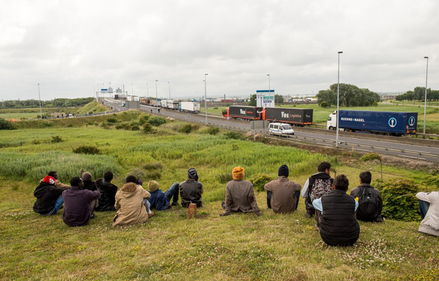 A group of people wait close to the road that leads to Eurotunnel. / Agencies,eurotunnel, july, migrants
