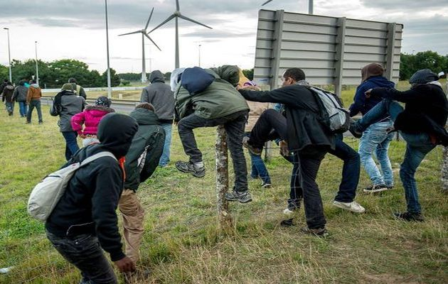 Migrants climb over a fence / Getty images,