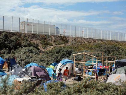 Migrants walk in a makeshift camp in Calais / AP
