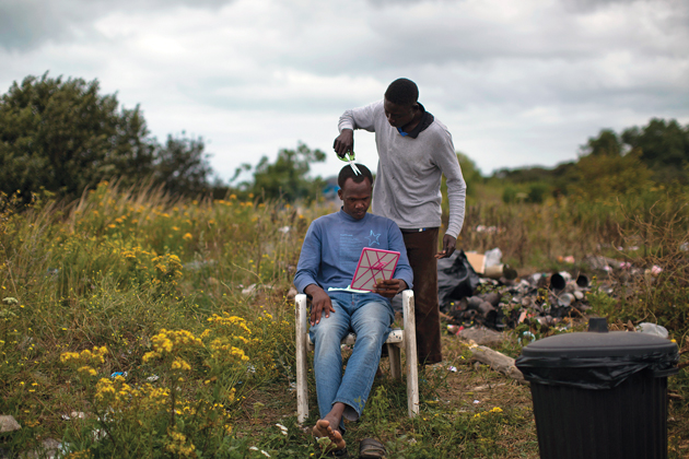 A Sudanese man gets a haircut at a camp near Calais early in August. / Photo: AP ,Calais, migrants, baptists, methodists, Church of Scotland, Cameron, Migration