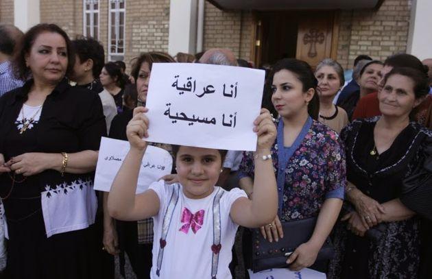 Iraqi girl holds a sign: 'I am Iraqi. I am a Christian.' ,