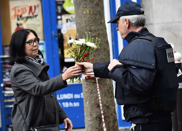 A woman gives flowers to a police man in Rue de Charonne. / AFP,Paris, citizens, attacks, terrorism