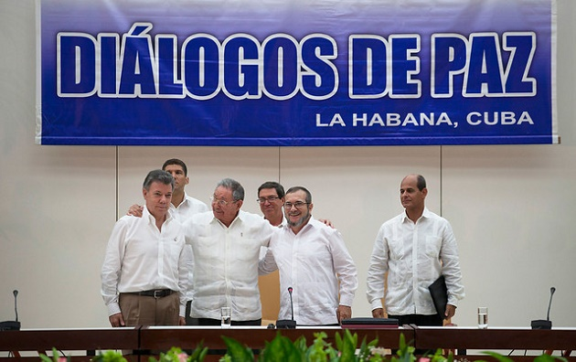 The moment President Juan Manuel Santos and a FARC representative announce the deal. / Colprensa,