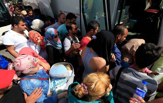 A group of asylum seekers boards a bus start trip to Hungary. / Reuters,