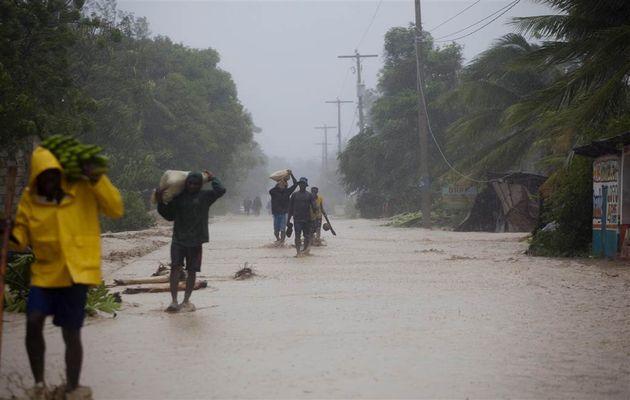 Residents walk in flooded streets as they return to their homes in Leogane, Haiti. /AP,hurrican matthew, haiti