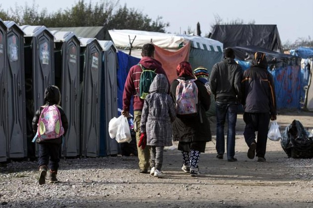 A group of people leave the Calais camp. / AFP,migrants, calais, october, uk