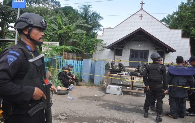 Police stand outside the church after the attack. / Reuters,