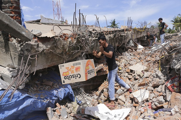 A man removes a box of food from under the rubble of a building that collapsed after an earthquake in Pidie Jaya, Aceh province, Indonesia, Wednesday, Dec. 7, 2016. / AP,