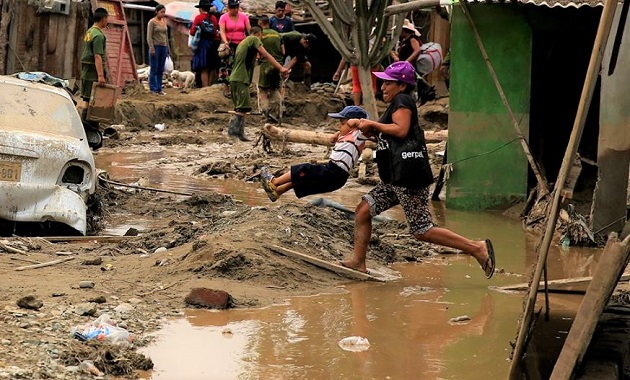 A woman and her child crosses a flooded road in Peru. / Reuters,