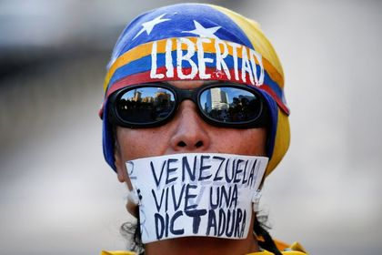 Freedom, Venezuela lives a dictatorship, a protester poster reads. /Reuters