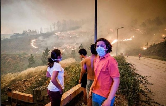 A group watches how firefighters fight the flames in Pedrógão Grande. / Global Imagens,