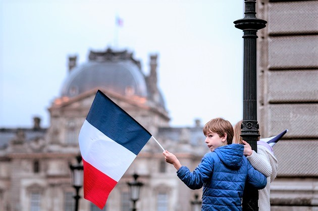 A boy holds a French flag in Paris. / Laurie Schall (Flickr, CC),France