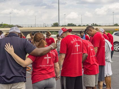 Former inmates and police praying together./ CHARM