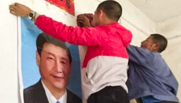 Men put up a poster of Chinese President Xi Jinping in a home in Yugan. / Lvv2.com, South China Morning Post,