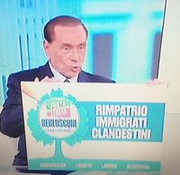 Berlusconi in a debate, holding a poster that says: repatriation of illegal migrants. / V.Rossato