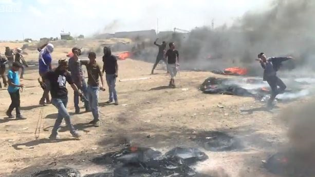 Palestinian protesters throw stones and burn tyres in Gaza, protesting against the opening of the US embassy in Jerusalem, May 14. /  BBC,