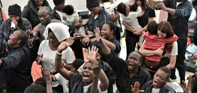 People on board of the Aquarius raise their hands in prayer as they arrive in Valencia, after 8 days. / Levante,