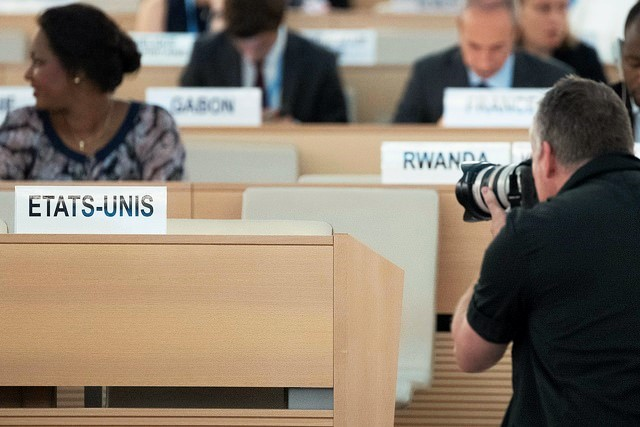 A photographer tak a photo of the plate of the United States of America at the 38th Regular Session of the Human Rights Council. 20 June 2018. / UN Photo, Jean-Marc Ferré (Flickr, CC),