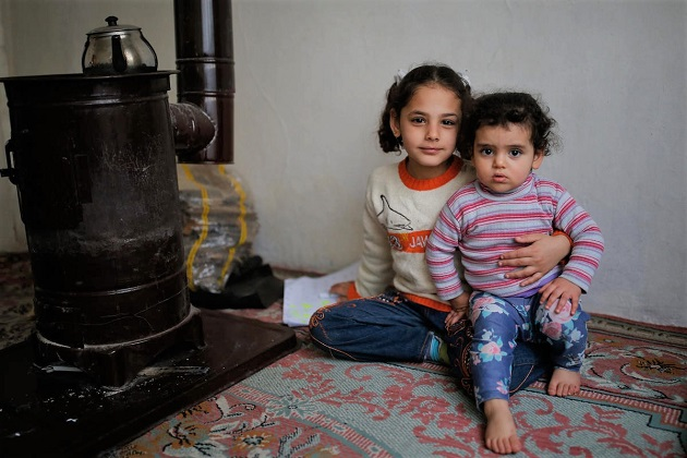 Seven-year-old Vahide holds her baby sister in their family home in Istanbul. / C UNHCR, Emrah Gurel,