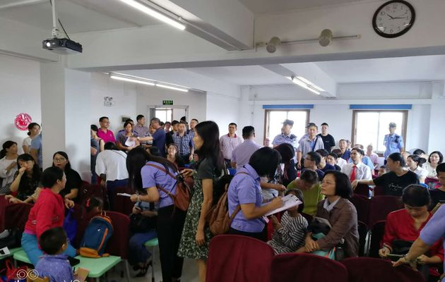 Uniformed officials take down personal information from Christians attending Bible Reformed Church in Guangzhou on July 15. / ChinaAid,