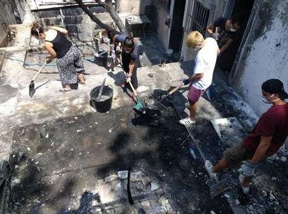 Chritians are helping with cleaning of the burnt properties. / Nikos Stamoulis.