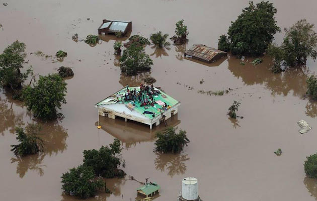 A group of people wait for help in a flooded area. / UEBE,