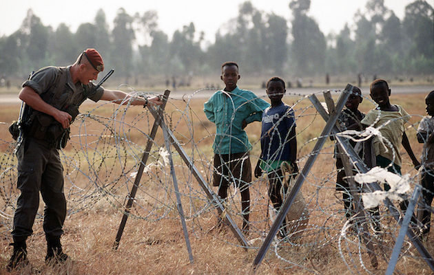 An  international soldier adjusting a wire fence in front of a group of refugee Tutsi children in 1994. / Wikimedia Commons,