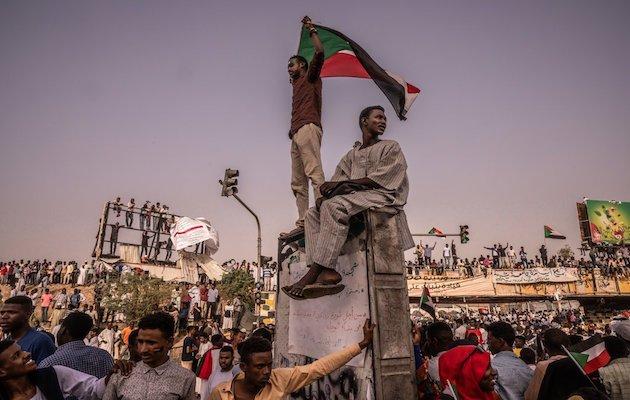 A protester flies a flag of Sudan in Khartoum. / Twitter @Malmakiyat, Bryan Denton,