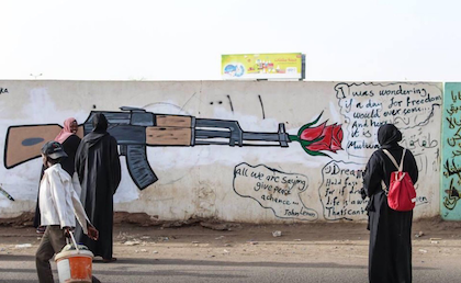 Two women look at graffiti of a gun and a rose in Khartoum. / Twitter @Safiaib38469578