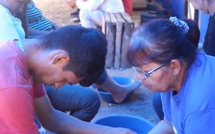 Volunteers pray with the walkers. / Video capture.