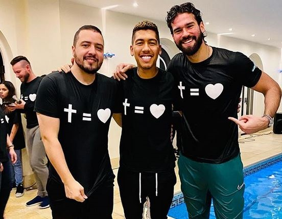 Roberto Firmino, centre, and teammate Alisson, right, after the baptism. / Instagram @roberto_firmino,