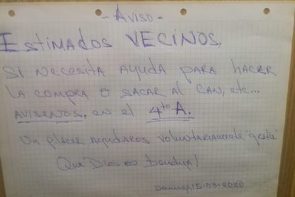 A poster in the main entrance of the building, offering help to their neighbors.