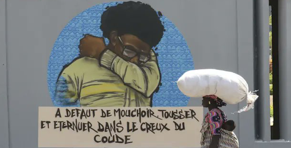 A Senegalese woman walks with her baby in front of graffiti that explains the need to cover your mouth and nose when you sneeze. / Twitter @Sinelo1968, Alaattin Dogru,