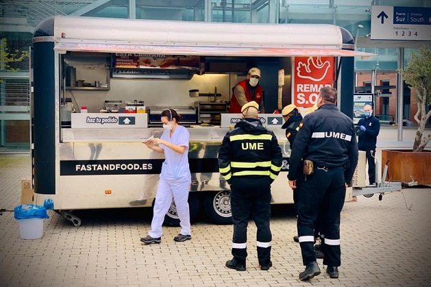 A nurse picks up her lunch from the REMAR food stand located at the entrance of the IFEMA, as Military Emergencies Unit (known as UME in Spanish) personnel wait their turn. / Remar via Actualiada Evangélica,