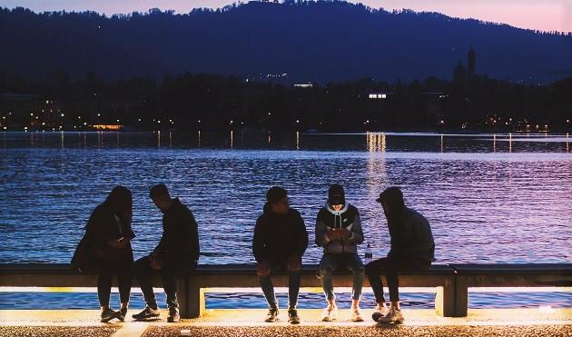 Young people using their smartphones in Zurich, Switzerland. / Wyron A (Unsplash, CC0),