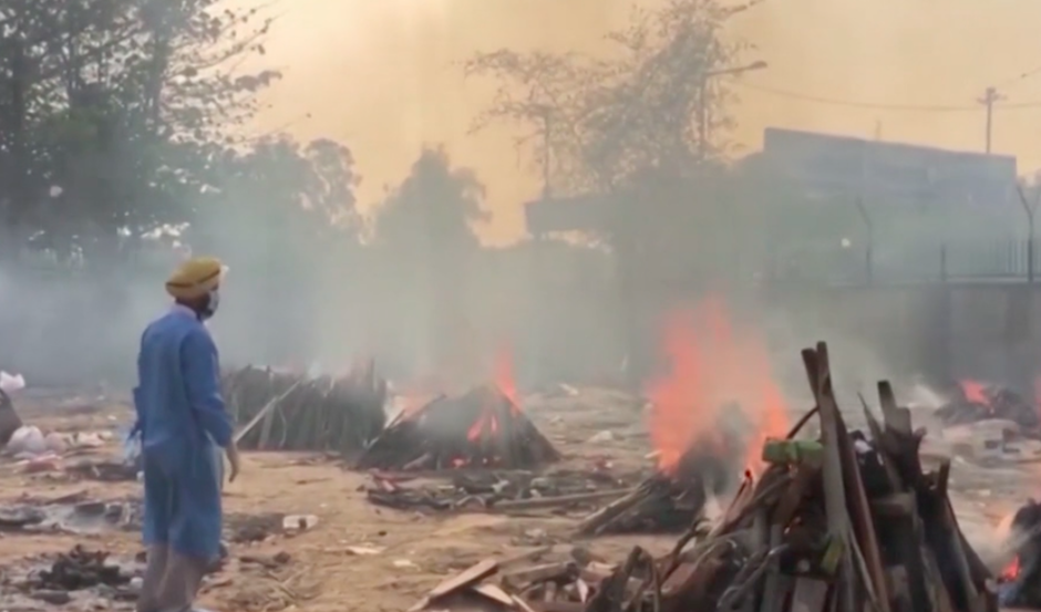 A health worker supervises outdoor cremations in Delhi. / Photo: Screenshot BBC.,