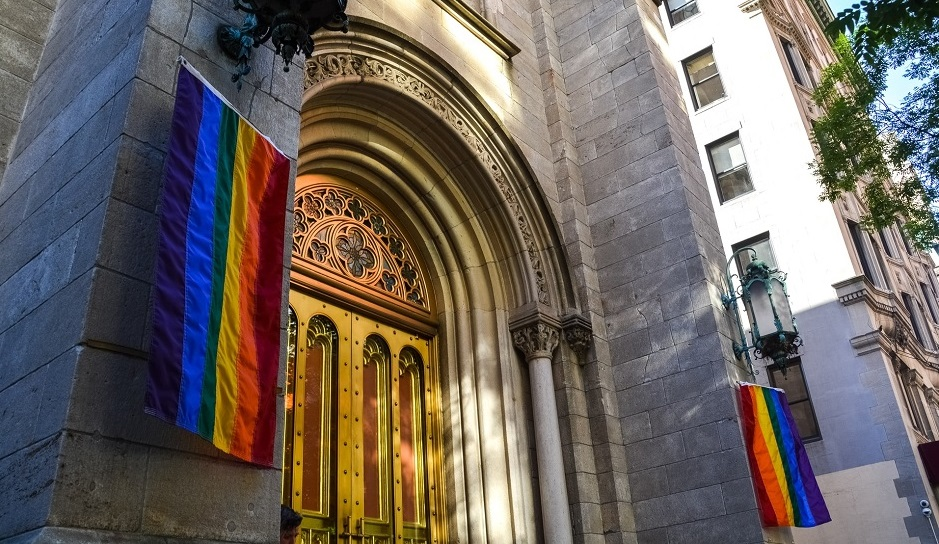 """A curch building in New York with LGBT flags. / Photo: <a target=""""_blank"""" href=""""https://unsplash.com/@jeremy0""""></a>, Unsplash, CC0.,"""